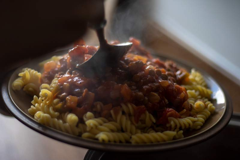 Ragu being served on pasta