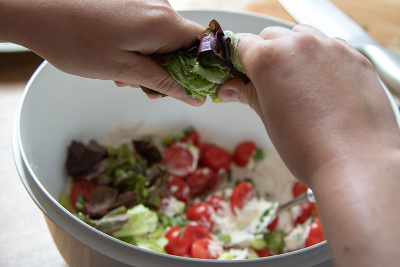 Tearing lettuce leaves into the salad and creme fraiche mix